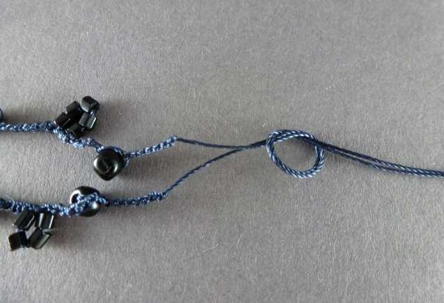 21. Wenn Sie alle Perlen verhäkelt haben, schneiden Sie das Garn ca. 10cm lang ab und ketten ab, so daß die Maschen sich nicht mehr auflösen können. Nehmen Sie Anfang und Ende des Garns zusammen und verknoten Sie es. Noch nicht festziehen!