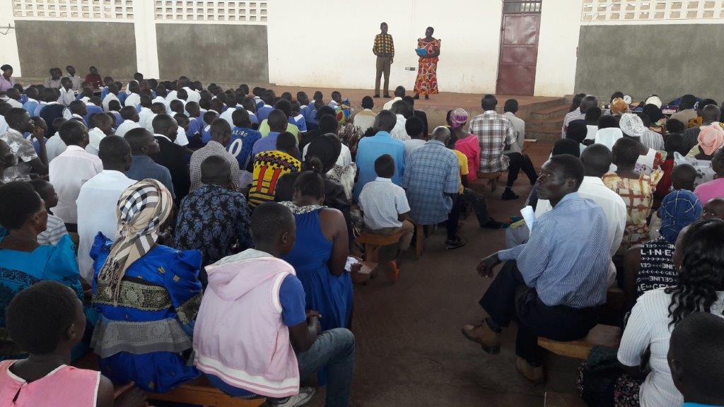 Grace hält eine mahnende Rede in Englisch. Sie wird auf Tschpadola übersetzt, der Stammessprache in Tororo