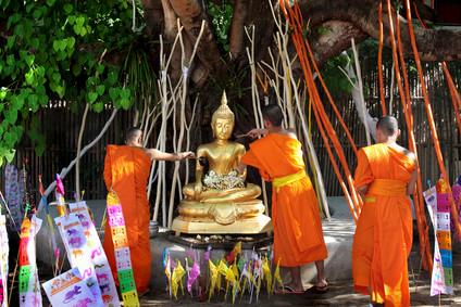 Mönche begießen eine Buddha-Statue mit Wasser