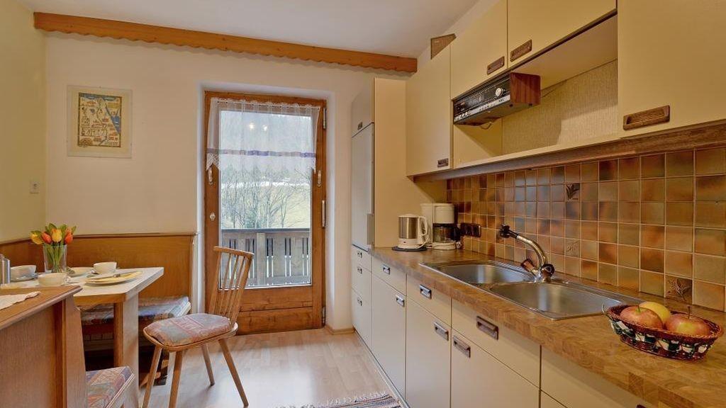 Küche mit Sitzecke und Zugang zur großen Dachterrasse