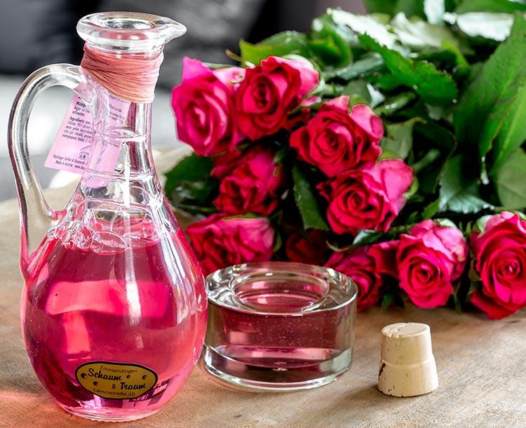 Haslinger Rosenschaumbad in einer wunderschönen geöffneten Glaskaraffe mit Henkel, der Korkverschluß liegt daneben, Menge für ein Vollbad ist in einem Glasbehälter abgefüllt deneben dekoriertStrauß mit roten Rosen, KOrkverschlu
