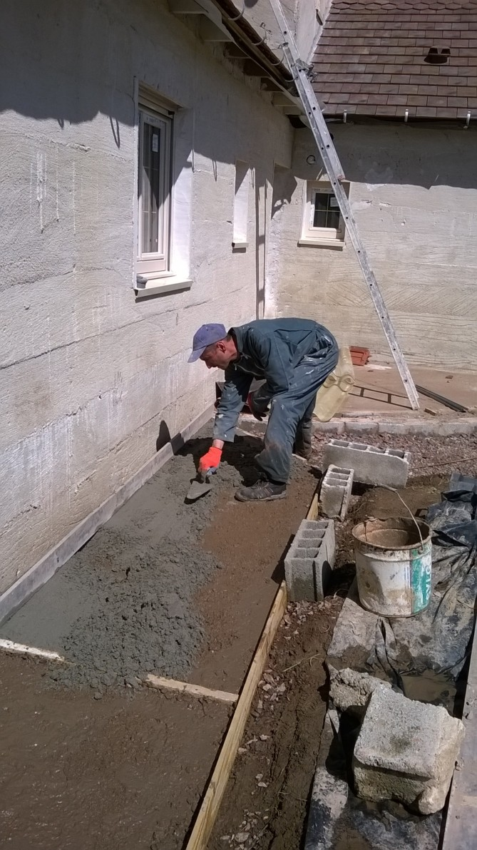 Tout le périmètre de la maison est bordé d'un radier damé recouvert de béton puis de ciment
