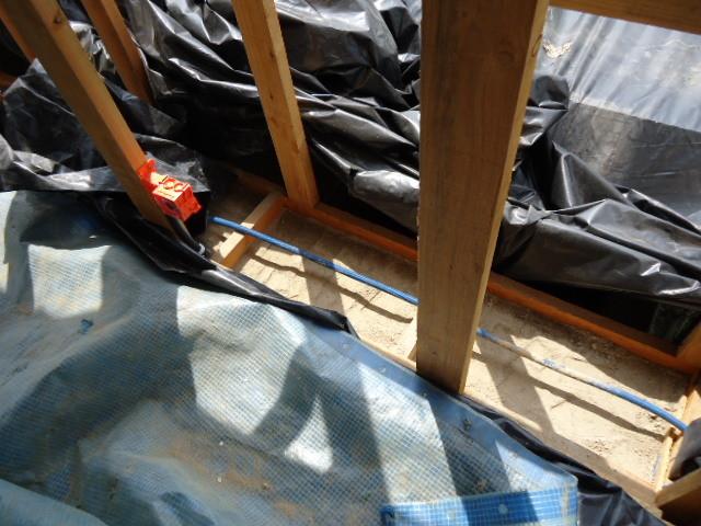 Le haut d'un mur intérieur en terre va être coiffé par le mortier et la paille