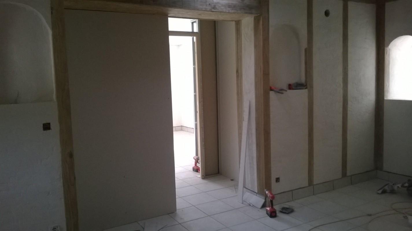 Le mur de refend en terre, une fois fini, garde l'ossature en douglas apparent recouvert de lasure.