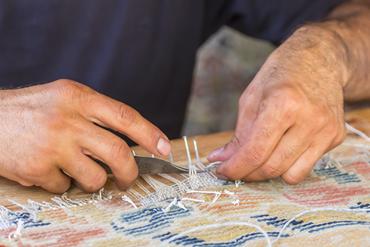 Der Rand eines kaputten Teppichs wird in Handarbeit neu gefasst.