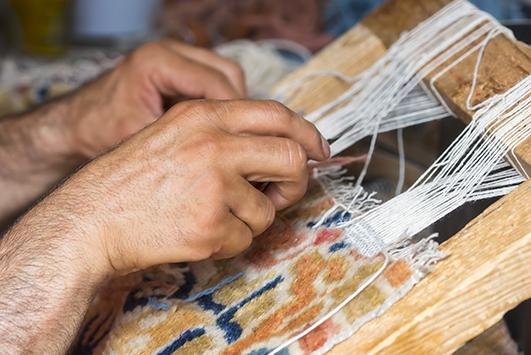 Defekte Ränder eines Teppiches werden bie der Teppichreparatur in Handarbeit neu geknüpft.