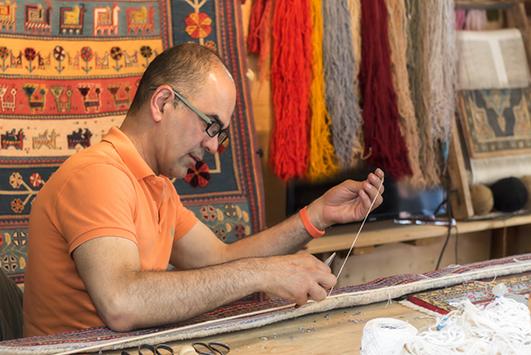 Behzad Djassemi beim Nähen eines Teppichs in der Werkstatt