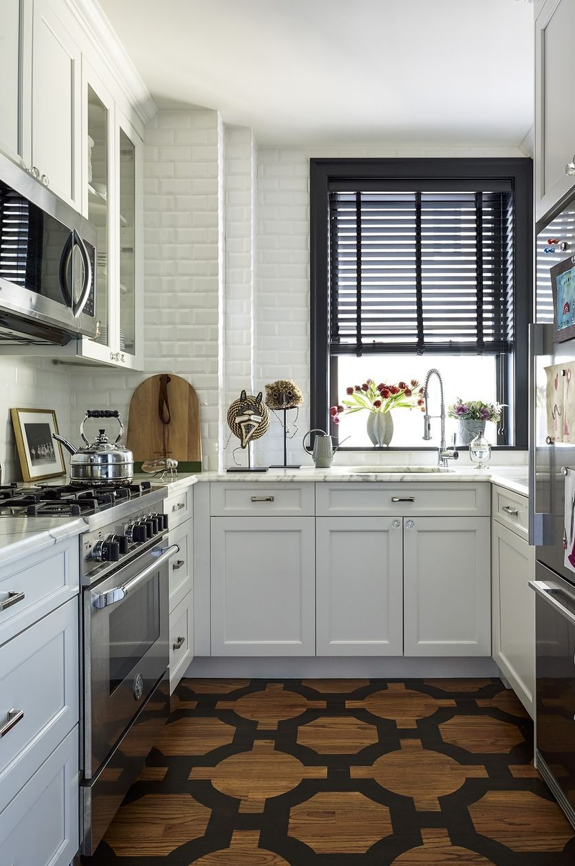 Stylish City Living Kitchen - The chic space contains a Bertazzoni oven, a Fisher & Paykel refrigerator, and marble counters. The subway tile is from Home Depot and the unique flooring is oak painted with a custom design.