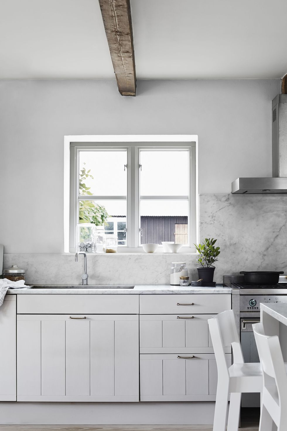 Grey and white hues add charm to a farmhouse kitchen design featuring a range, hood, and sink by Smeg, fittings by Vola, Carrara marble counters, and cabinetry painted in Farrow & Ball's Cornforth White.