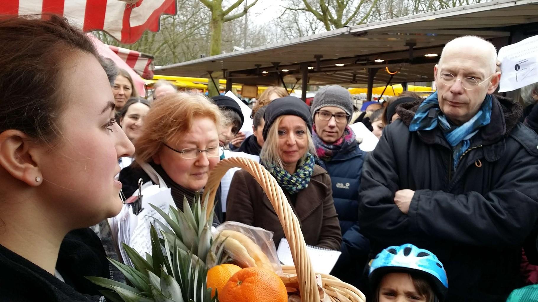 Marie Pigors (links), eine der Sprecherinnen der Markthändler, übergibt einen echten Findorffer Marktkorb an die Bürgerschaftsabgeordneten Ralph Saxe (rechts) und Heike Sprehe sowie an die VertreterInnen des Findorffer Beirates.