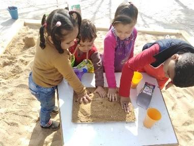 يقوم الأطفال بطبع الأشكال والرسم على الرمل في صحن.