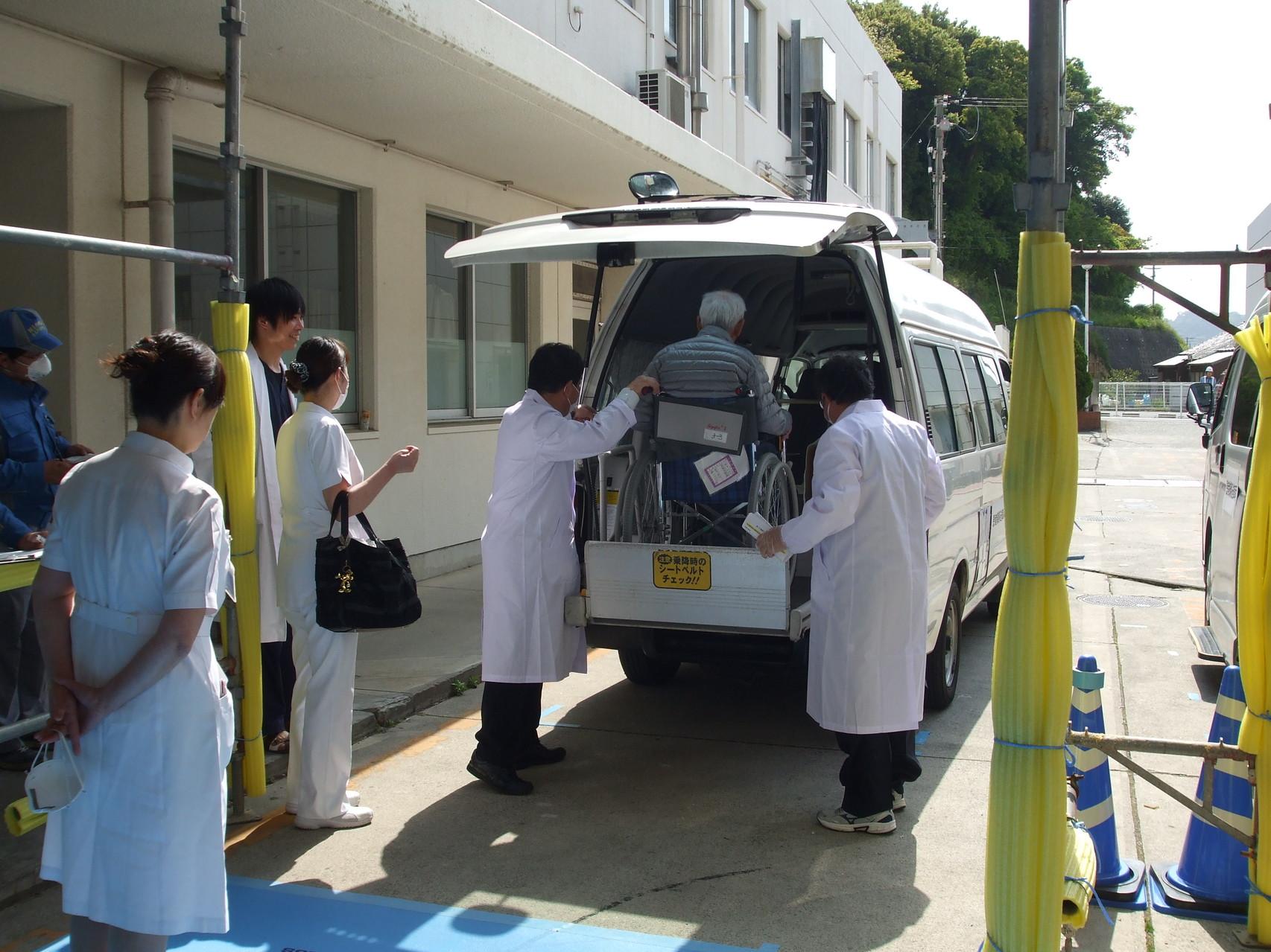 搬送スタッフにより車両に患者様が車椅子ごと乗車中