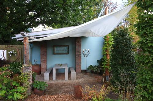 Schattenplatz: unter Nachbars Eiche liegt diese überdachte Terrasse - hier ergänzt mit Sonnensegel