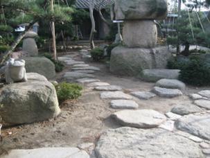 天然の安田産御影石を既存の飛び石と調和するよう設置しました。