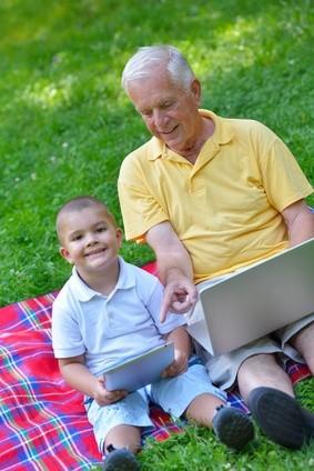 Großvater und sein Enkel mit Laptop und Tablet