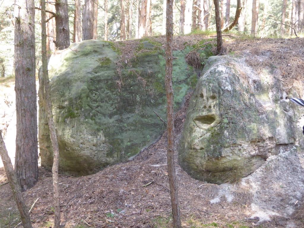 Dämonische Fratzen an den Felsen seitlich des Durchganges