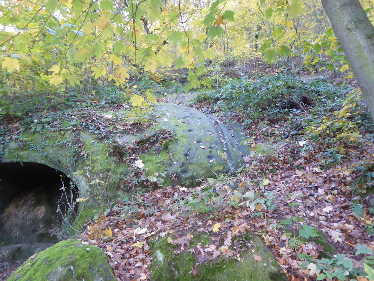 Der Fels neben der Grotte mit Trittmarken und Rinnen
