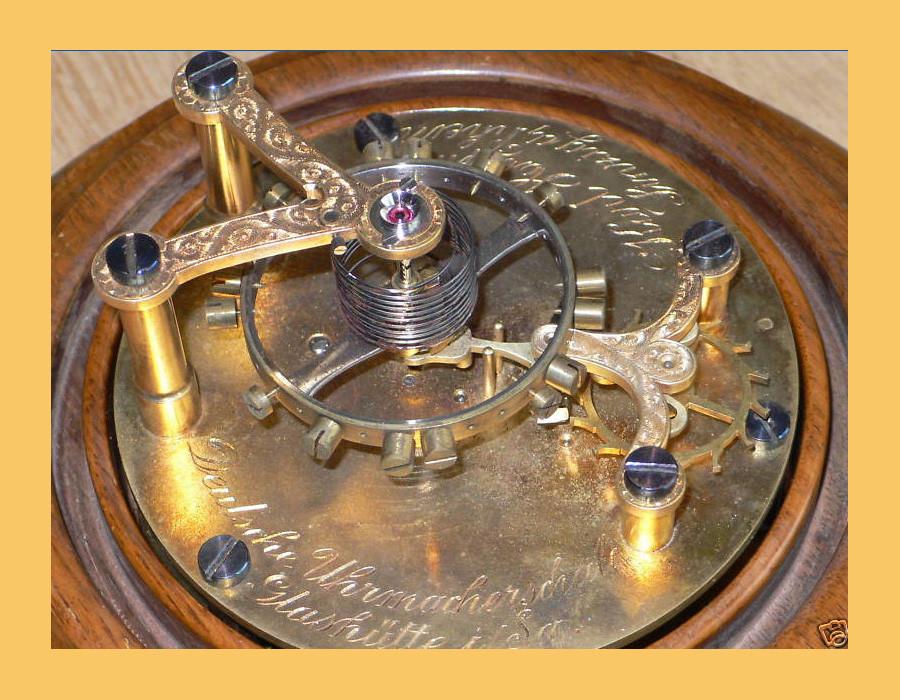 v.L.n.R. Handgravierter Unruhkloben mit gebläuten Schrauben, geschraubter Chaton für den Rubin in dem die Unruhwelle läuft, Unruhreif & Aufzugsfeder, Anker, & Ankerrad deren Bewegung das ticken einer mechanischen Uhr hervorrufen.