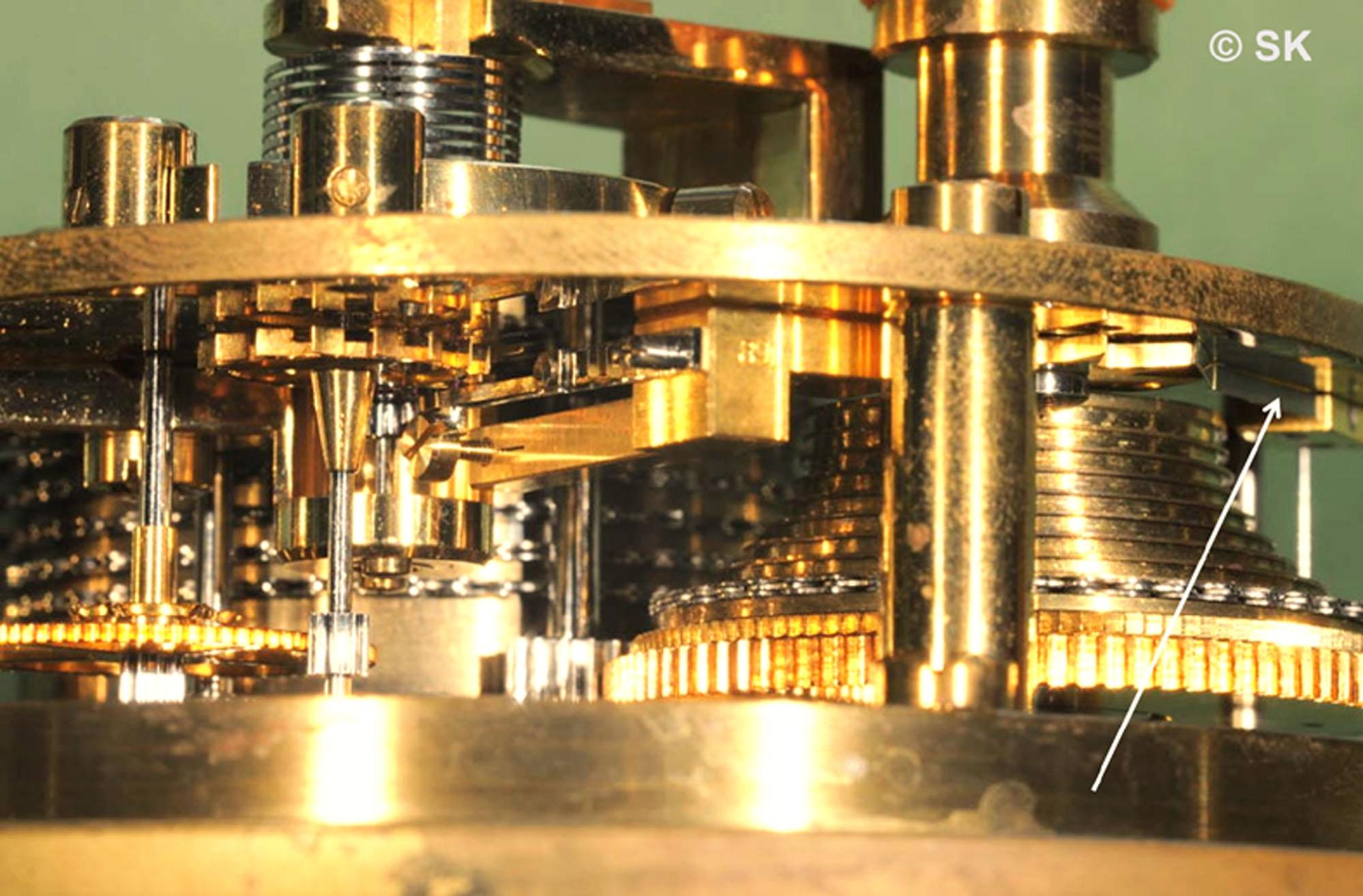 Der Pfeil zeigt auf das Teil, welches erst bei den Marinechronometern vorhanden ist, die in der Fertigung auf Zugband umgestellt waren