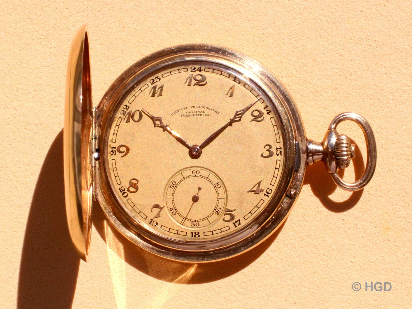 Vergoldetes Metallzifferblatt mit aufgesetzten Stundenzahlen und gedruckter 24 Stundenanzeige, abgesenktes Sekundenzifferblatt, vergoldete Kathedralzeiger