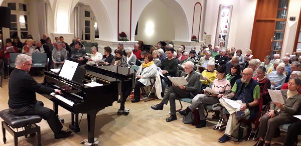 Begleitet von Thomas Sander am Klavier, singen die Gäste im vollen Saal der Musikschule Wetzlar Weihnachtslieder in mehreren Sprachen.