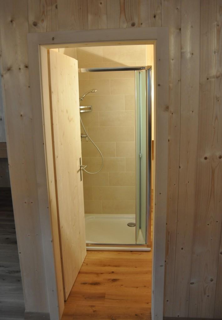 Eingang zum Bad mit Dusche im Hintergrund