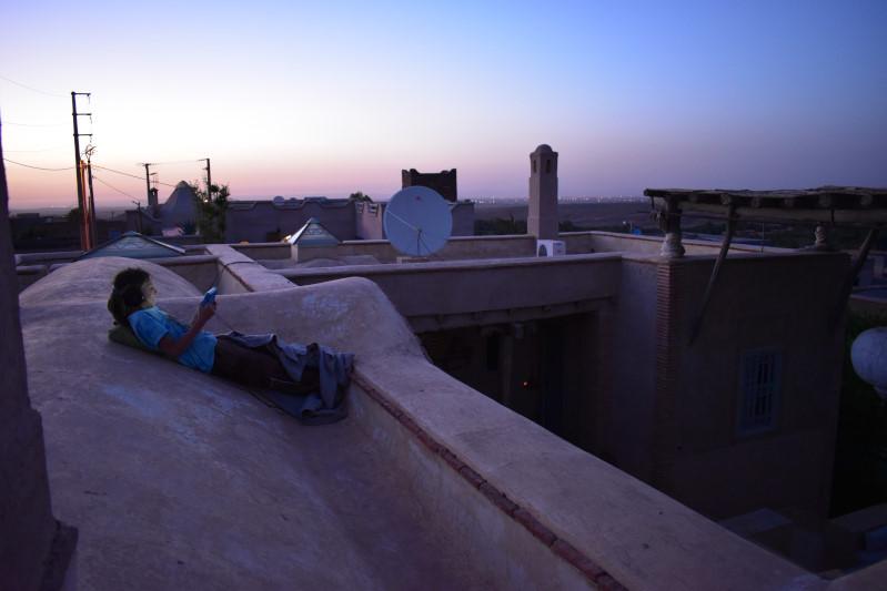 auf dem Dach bei Sonnenuntergang Tab gucken, hinten leuchtet Marrakesch