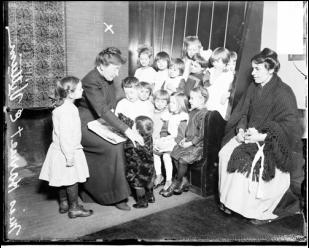 Харриет Виттам (с книгой) в окружении детей. Чикаго, 1914