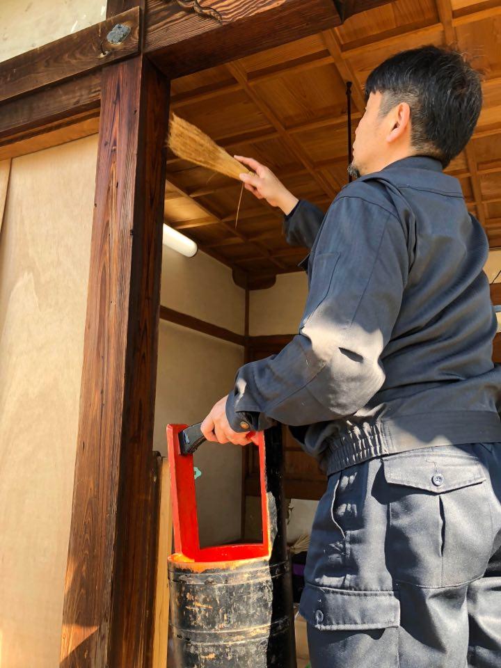 神社正面柱灰汁洗い施工中