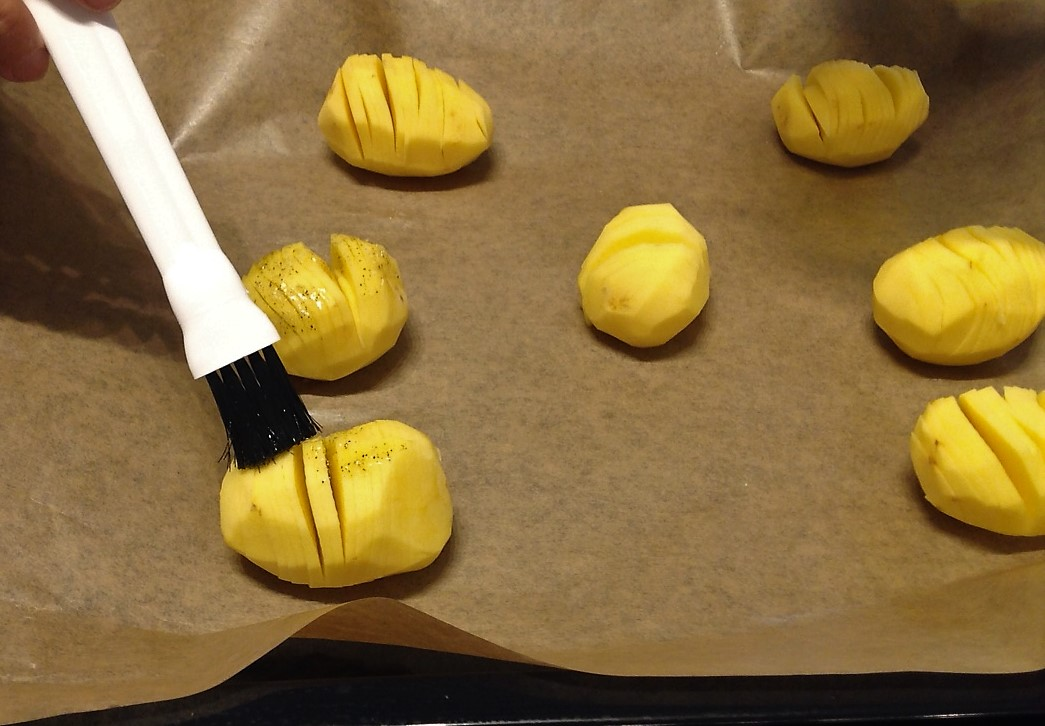 Legen Sie die eingeschnittenen Kartoffeln auf ein Backblech. Bepinseln Sie die Kartoffeln mit der Marinade, ziehen Sie dafür die Scheiben ein wenig auseinander, damit die Marinade etwas eindringen kann.