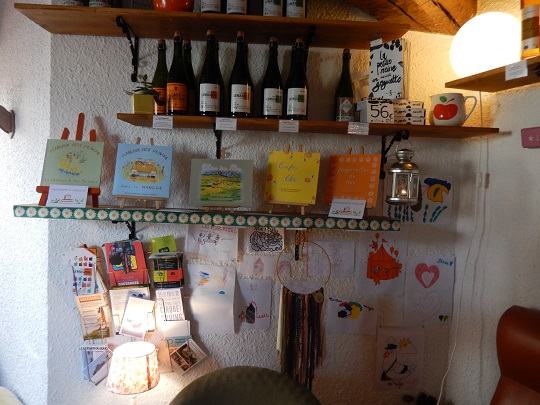 """Les beaux livres de Françoise Savereux, entre les bouteilles de cidre produit localement, les dessins d'enfants, et un attrappe-rêve réalisé par """"Elle a"""", une créatrice manchoise."""