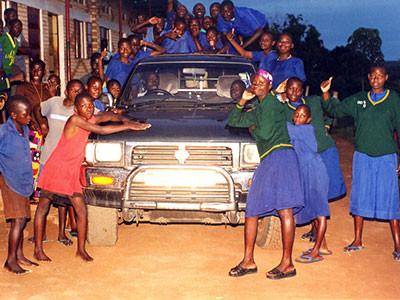 Kinder posieren vor und auf dem Auto