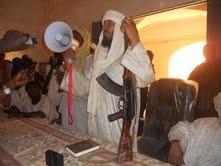 Ein Führer der MUJAO Bewegung bei einer Ansprache vor der Bevölkerung in GAO. Ein Mikrofon in der rechten eine Kalaschnikow in der linken Hand und vor ihm der Koran.