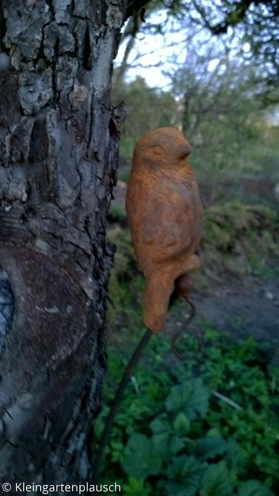 Dekospatz im Rost-Look vor Apfelbaum