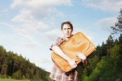 Mann mit Koffer auf dem Arm