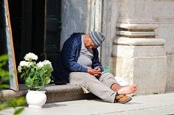 schlafender Mann ohne Strumpf draussen auf der Türschwelle