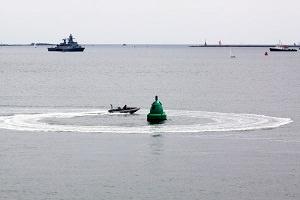 Boje im Wasser von Boot umkreist