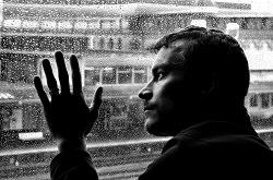 Mann an vollgeregneter Fensterscheibe