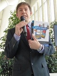 Mann sehr verkrampft hält eine Rede mit Buch in der Hand