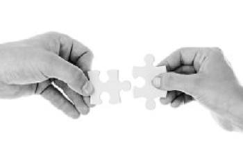 Zwei Hände reichen einander Puzzleteile