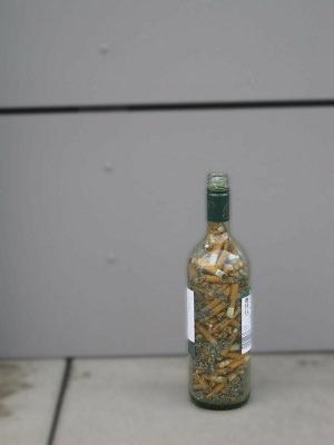 leere Weinflasche gefüllt mit Zigaretten