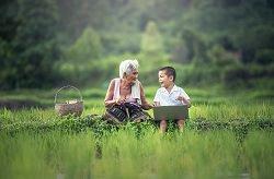alte Frau mit Kind und Notebook beim Picknick