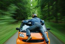 Mann fährt auf Motorhaube von Smart mit