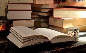 aufgeschlagenes Buch vor Bücherstapeln