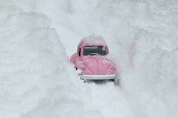 rosa Pkw steckt im Schnee fest -total festgefahren