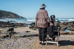 Zwei Frauen am Strand eine steht hinter der sitzenden