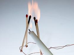 Kerze zündet Streichhölzer an