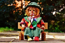 Clownspuppe auf einer Holzbank