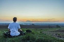 Junger Mann meditiert auf einer Anhöhe vor einer Landschaft