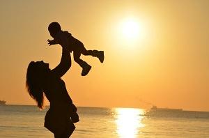 Frau mit Kind am Strand vor Sonnenuntergang